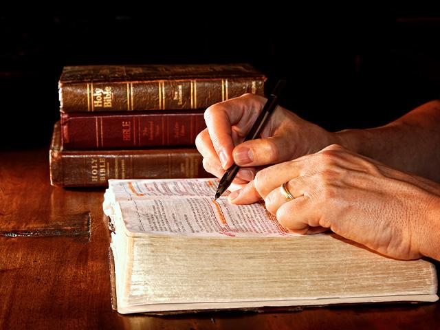 open Bible studying with a pen marking lines of scripture
