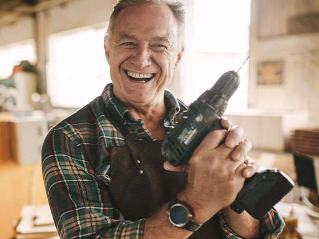 senior man smiling with power drill in his hand