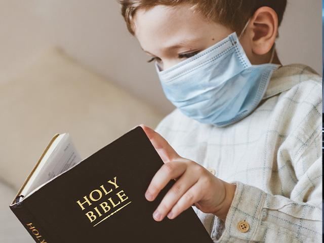 child wearing surgical mask reading the Bible