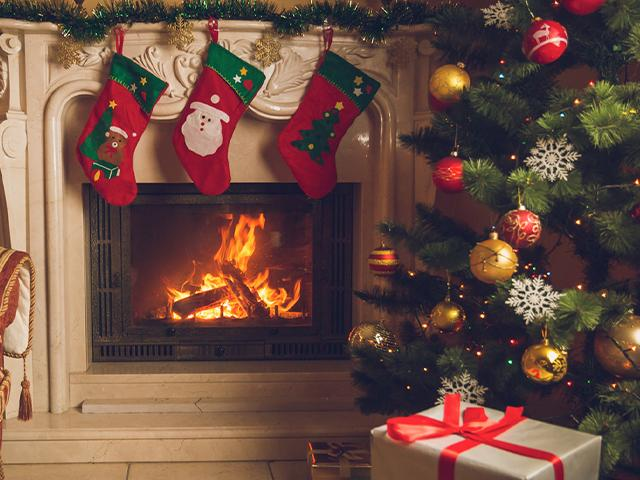 christmas stockings hanging above a fireplace next to a christmas tree