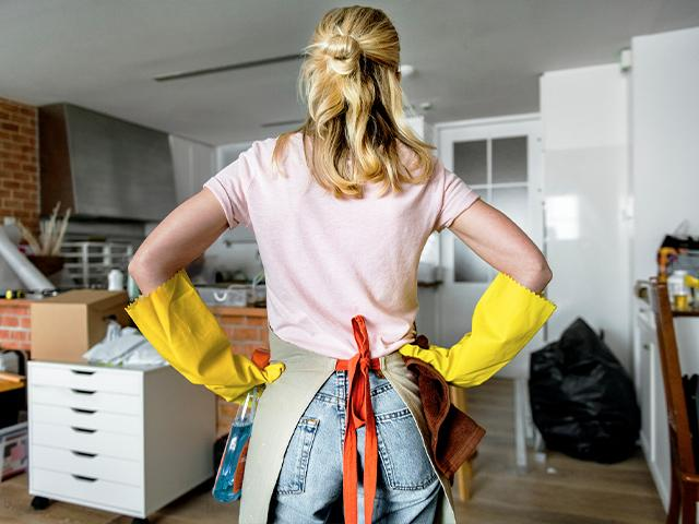 woman wearing cleaning gloves facing a room of clutter