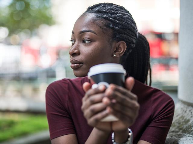 woman holding a cup of coffee and thinking about something