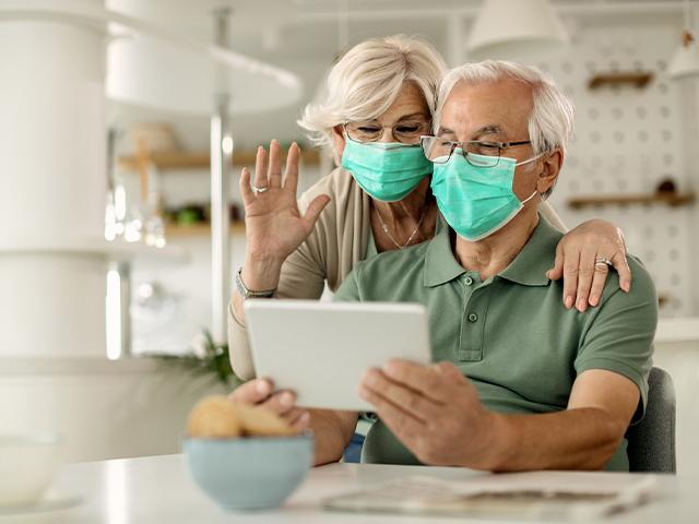 senior couple wearing facemasks and video chatting on tablet