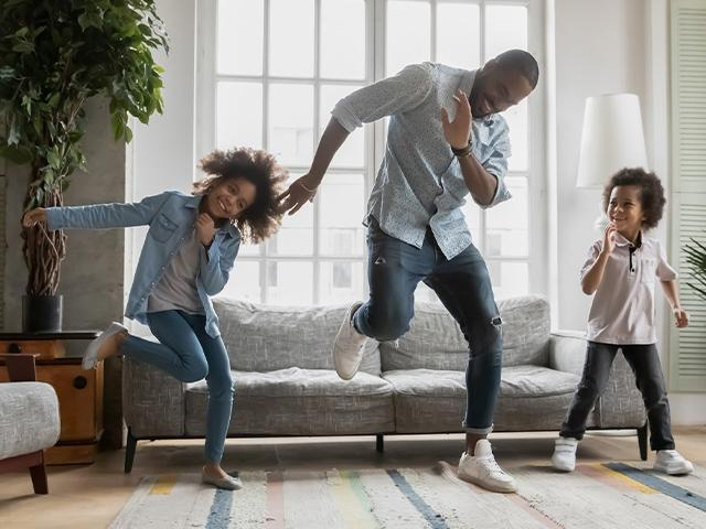 two children dancing with their father