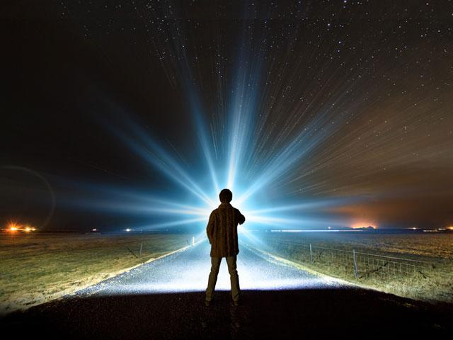 boy with flashlight walking down dark road