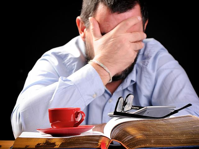 man sitting at desk with coffee cup on an open book and head in his hands