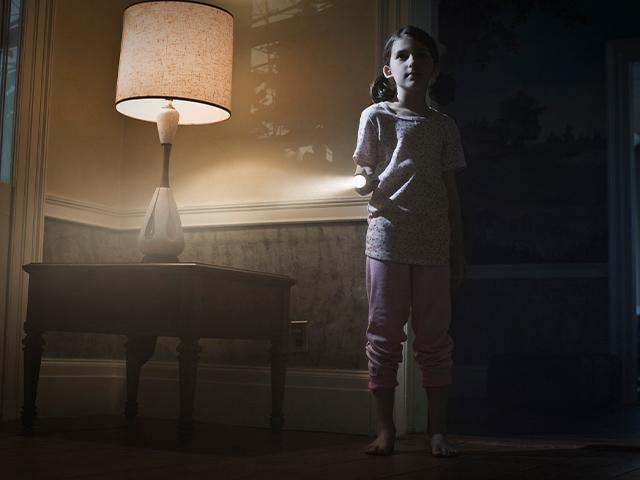 young girl in a dimly lit room with a table lamp