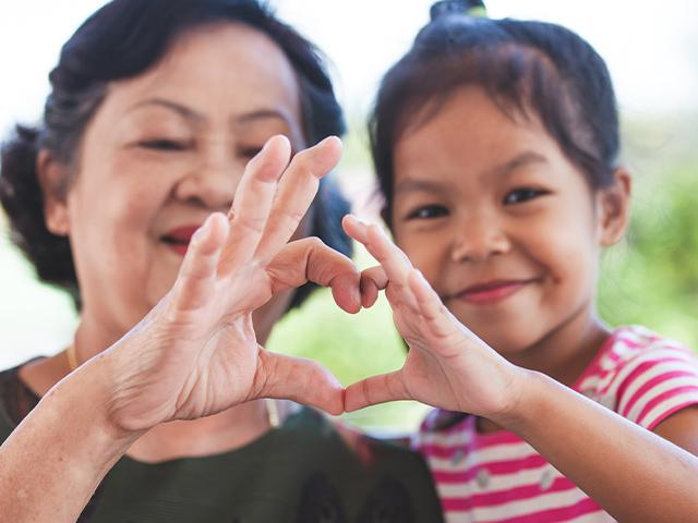 grandmother and child making heart sign together with their fingers