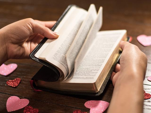 thumbing through a Bible with heart cut outs strewn on the table