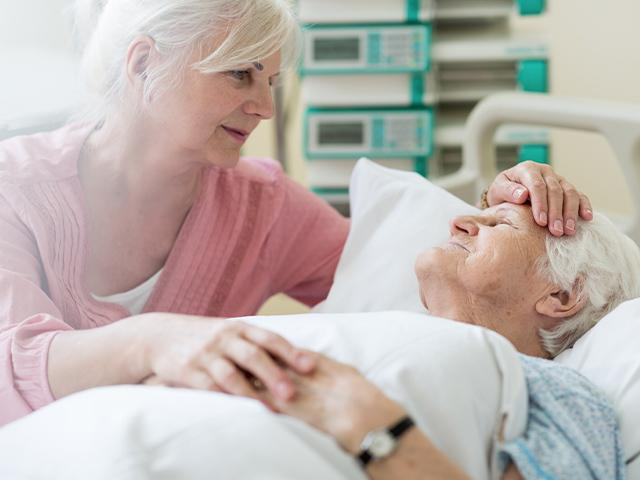 adult daughter visiting mother in hospital