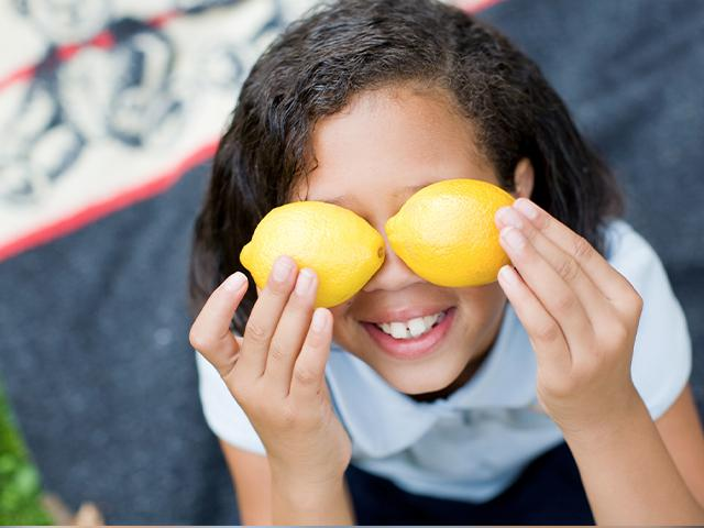 girl smiling and covering her eyes with bright yellow lemons