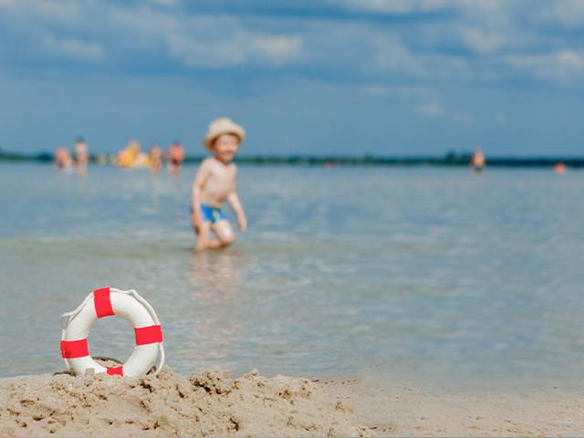 lifebuoy on beach and young boy in the shallow water
