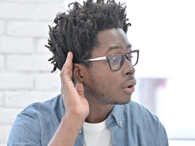 man with his hand cupped up to his ear to listen