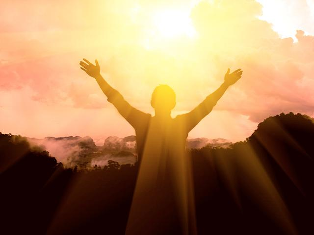 man thanks God with raised arms toward the light shining through the clouds