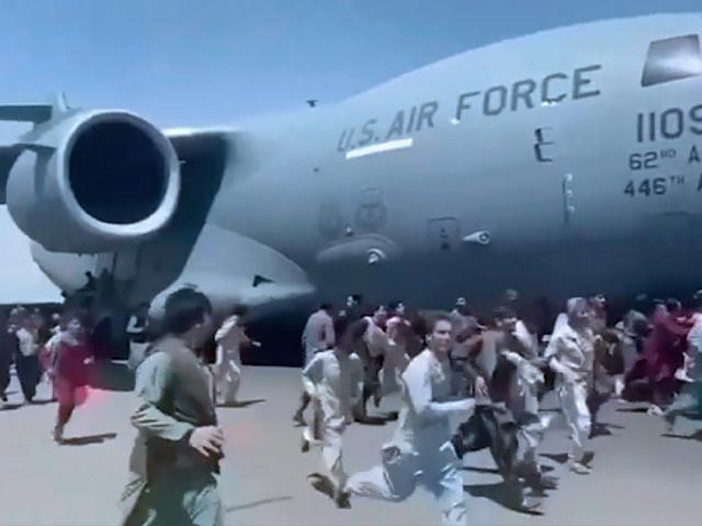 Thousands of Afghans rushed onto the tarmac of Kabul's international airport, some so desperate to escape the Taliban capture of their country that they held onto an American military jet as it took off and fell to their death. (Verified UGC via AP)