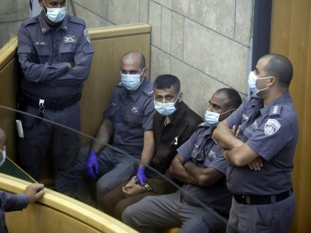 Mohammed Aradeh, center, is surrounded by guards in a courtroom in Nazareth, Israel, after he and three other Palestinian fugitives were captured on Saturday, Sept. 11, 2021. (AP Photo/Sebastian Scheiner)