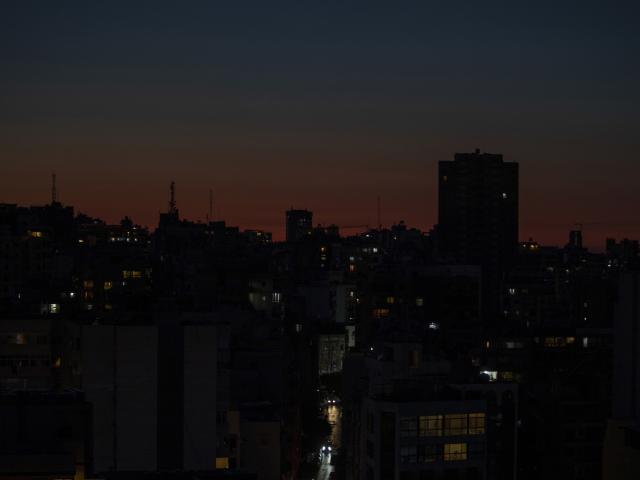 n this Monday, March 29, 2021 file photo, the capital city of Beirut remains in darkness during a power outage as the sun sets, in Lebanon.  (AP Photo/Hassan Ammar, File)