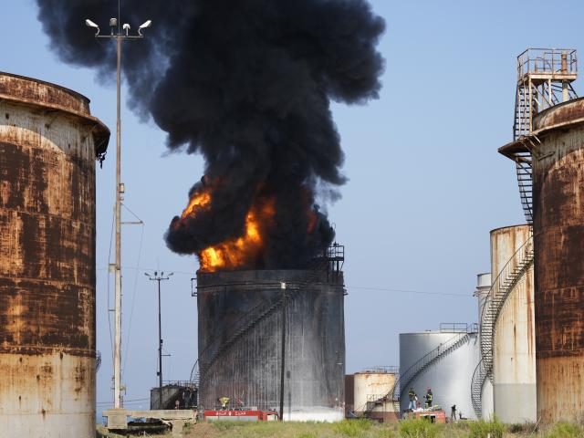 Firefighters work to extinguish a fire in an oil facility in the southern town of Zahrani, south of the port city of Sidon, Lebanon, Monday, Oct. 11, 2021. A huge fire broke out at an oil facility in southern Lebanon's coastal town of Zahrani, but the cau