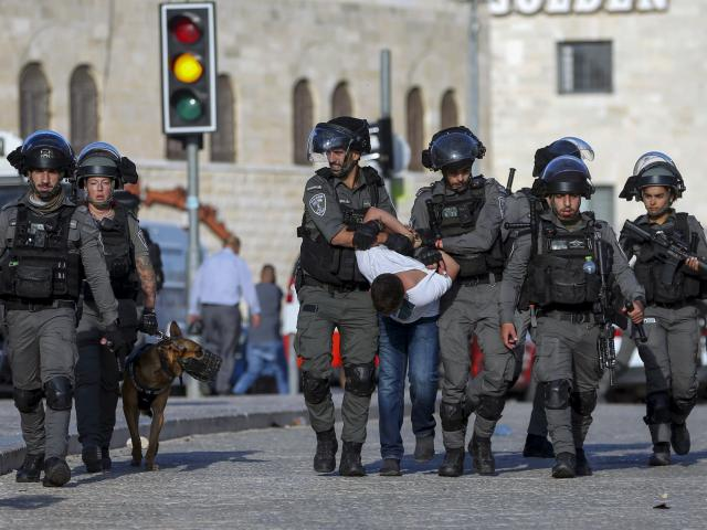 Israeli border police officers detain a Palestinian youth during clashes between Palestinians and Israeli police as thousands of Muslims flocked to Jerusalem's Old City to celebrate the Prophet Muhammad's birthday, Tuesday, Oct. 19, 2021. (AP Photo/Mahmou
