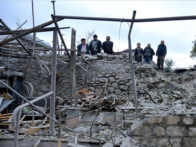 Men look at the damage in a residential area after shelling by Azerbaijan's artillery during a military conflict in self-proclaimed Republic of Nagorno-Karabakh, Sunday, Oct. 4, 2020.David Ghahramanyan/NKR InfoCenter PAN Photo via AP)
