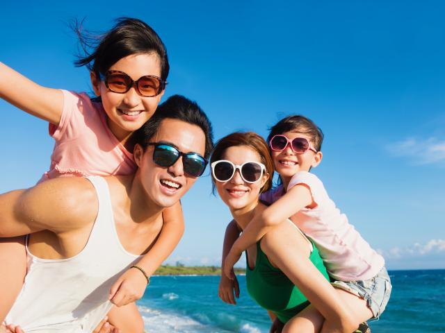 Happy family on beach wearing sunglasses