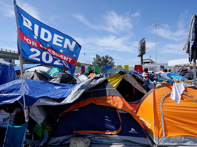A campaign flag for President Joe Biden flies over tents at a camp of migrants at the border port of entry leading to the U.S., March 17, 2021, in Tijuana, Mexico. (AP Photo/Gregory Bull)
