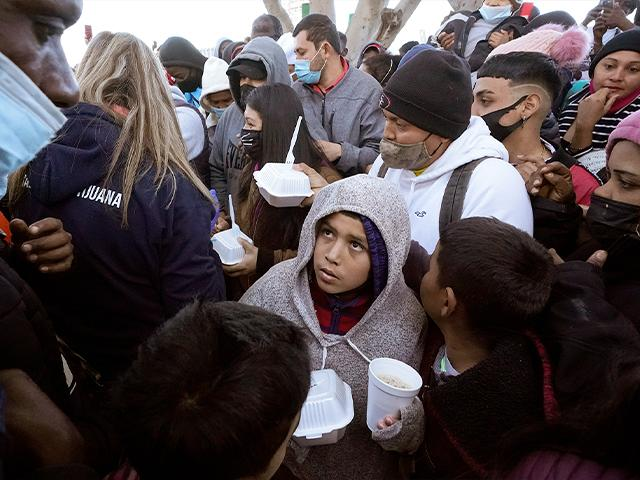 Asylum seekers receive food as they wait at the border in Tijuana, Mexico. (AP Photo/Gregory Bull)