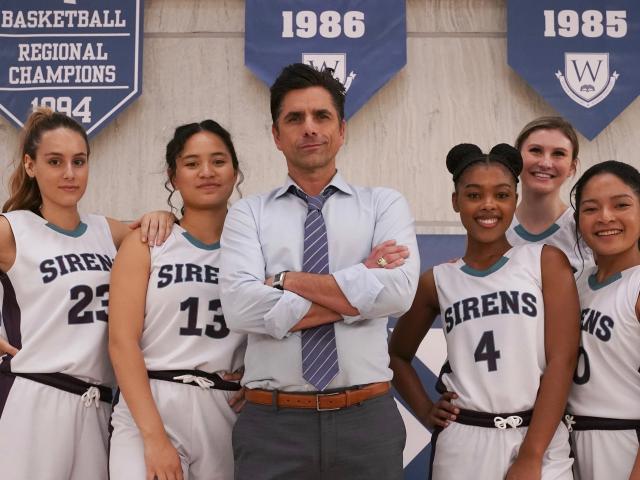 Big Shot movie on Disney+ John Stamos standing with girls basketball team on basketball court