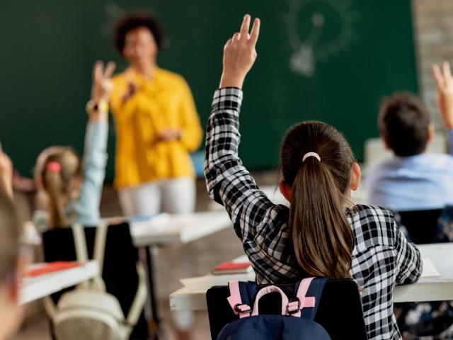 Classroom full of kids with teacher wearing yellow shirt