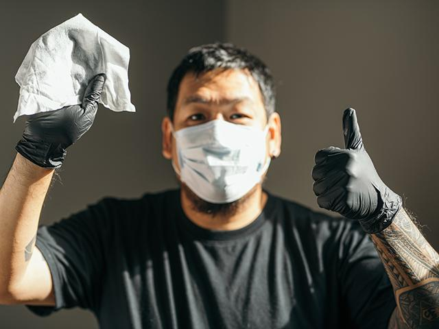 man wearing a mask and gloves holding up a disinfectant wipe