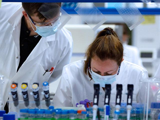 Lab technicians working on a coronavirus vaccine at Johnson & Johnson subsidiary Janssen Pharmaceutical in Beerse, Belgium, June 17, 2020. (AP Photo/Virginia Mayo)
