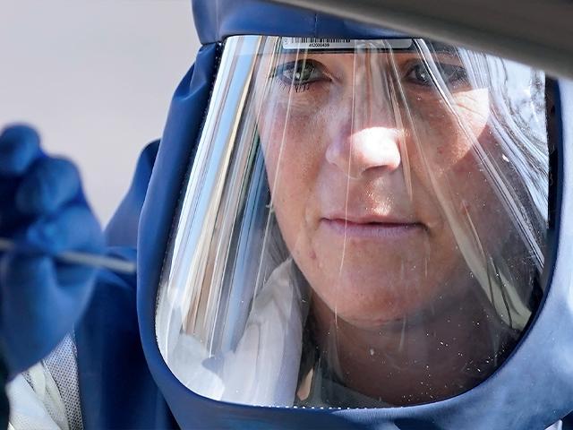 Public health nurse performs a coronavirus test. (AP Photo/Rick Bowmer)