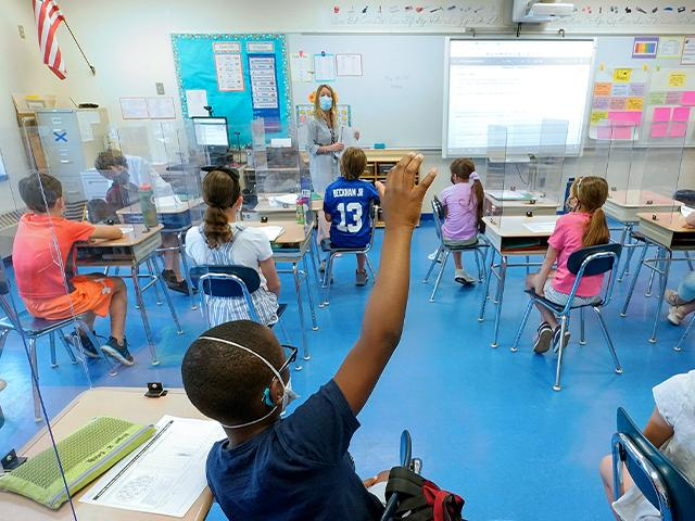 A teacher and her third grade students wear face masks and are seated with social distancing spacing (AP Photo/Mary Altaffer, File)