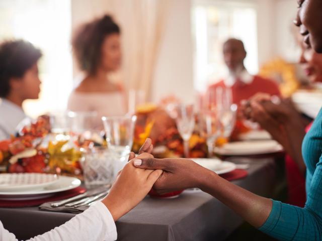 Family praying a blessing at dinner