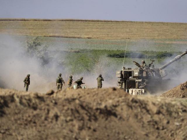 An Israeli artillery unit fires toward targets in Gaza Strip, at the Israeli Gaza border, Saturday, May 15, 2021. (AP Photo/Ariel Schalit)