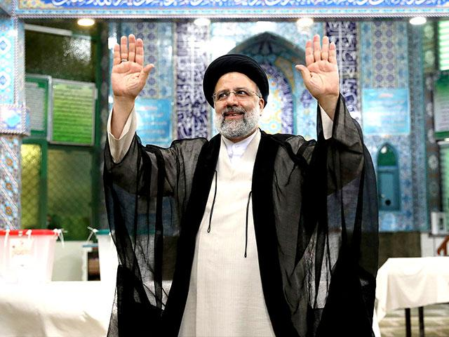 Ebrahim Raisi, a candidate in Iran's presidential elections waves to the media after casting his vote at a polling station in Tehran, Iran Friday, June 18, 2021. (AP Photo/Ebrahim Noroozi)