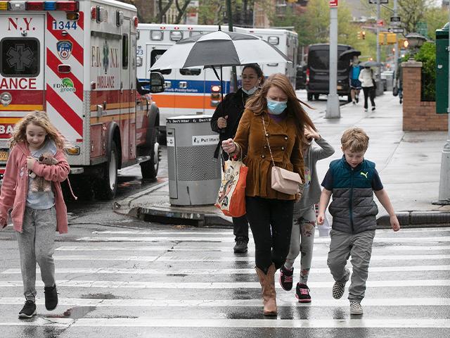 People walk by ambulances parked outside NewYork–Presbyterian Brooklyn Methodist Hospital, May 6, 2020 in New York during the coronavirus pandemic. (AP Photo/Mark Lennihan)