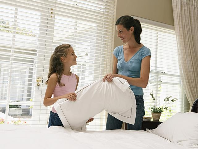 mother and daughter making a bed