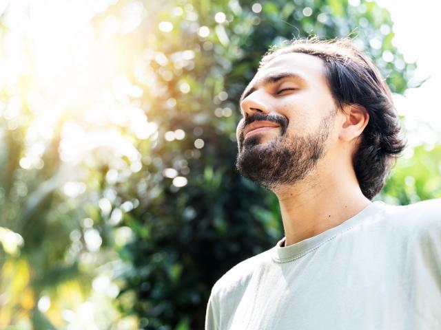 smiling man in sunlight forest