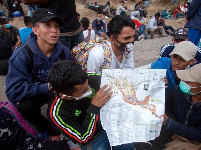 Honduran migrants show their route on a map of Mexico and Central America to reporters, as they sit near a police roadblock at a highway in Vado Hondo, Guatemala, Jan. 17, 2021. (AP Photo/Sandra Sebastian)