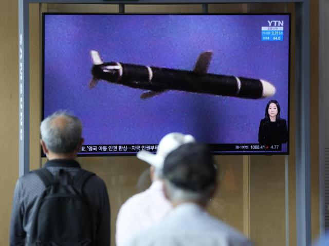 """People watch a TV screen showing a news program showing a North Korean handout photo that says, """"North Korea's long-range cruise missiles tests."""" (AP Photo/Lee Jin-man)"""