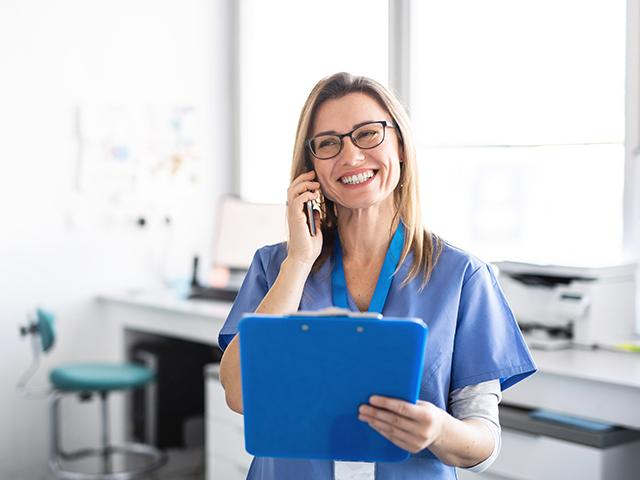smiling nurse talking on phone and holding a tablet