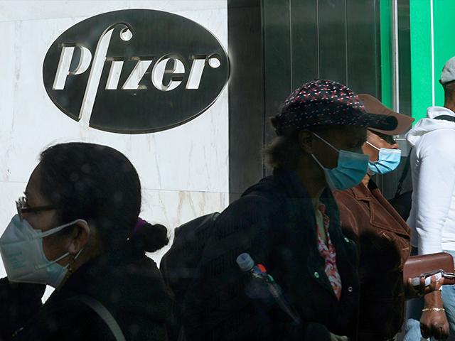 Pedestrians walk past Pfizer world headquarters in New York on Monday Nov. 9, 2020.