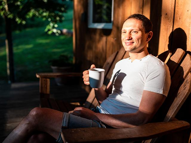 man sitting in a chair on the front porch having coffee