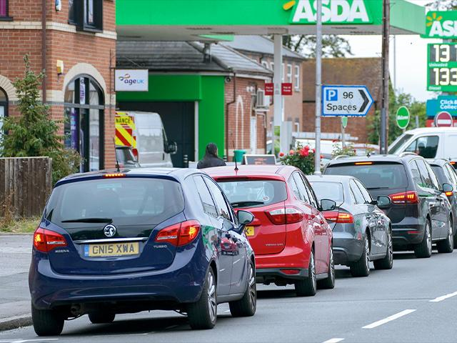 Cars queue outside a petrol station in Reading, England. Motorists have formed long lines as they try to fill up in case of further disruption. (Steve Parsons/PA via AP)