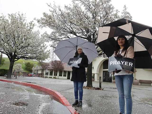 Martha Valdivia, left, and Maria Munoz wait for cars to offer drive up prayer service outside of The Bay Church in Concord, Calif., Sunday, March 15, 2020. (AP Photo/Jeff Chiu)
