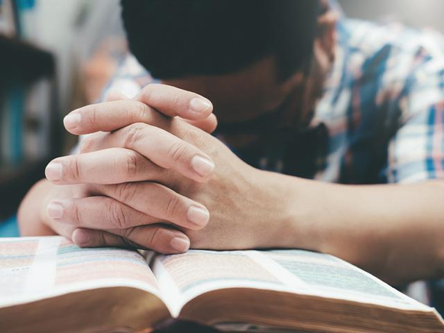 man praying with hands overtop an open Bible