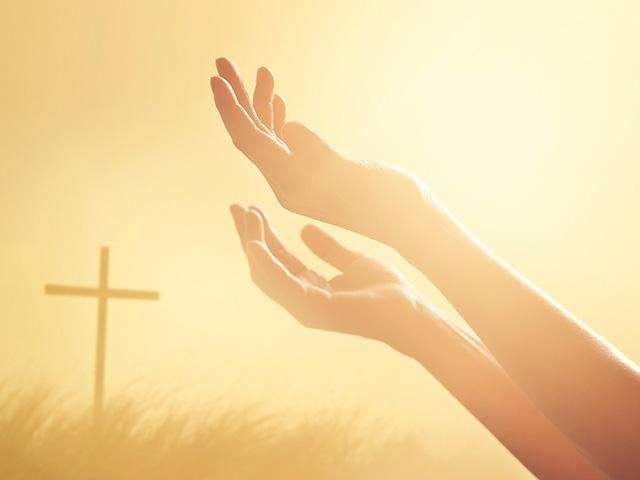 hands raised toward almighty God and a cross in the background