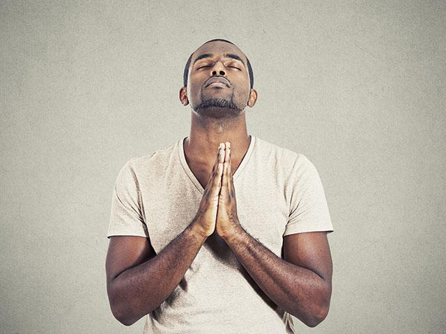 man praying eyes closed