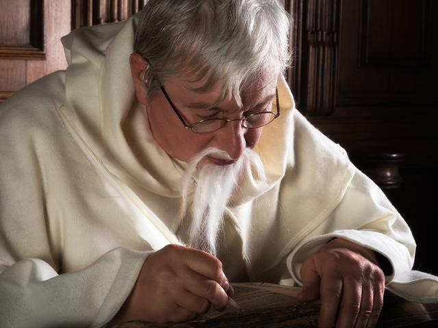 monk writing with a quill pen
